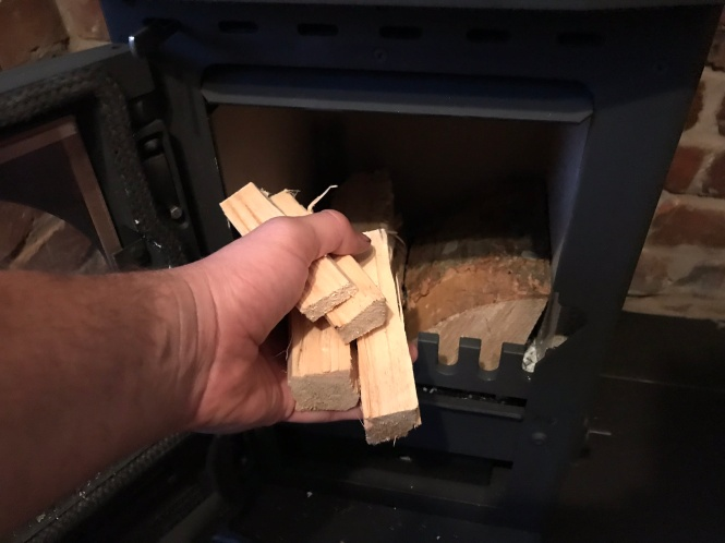 putting kindling into a stove